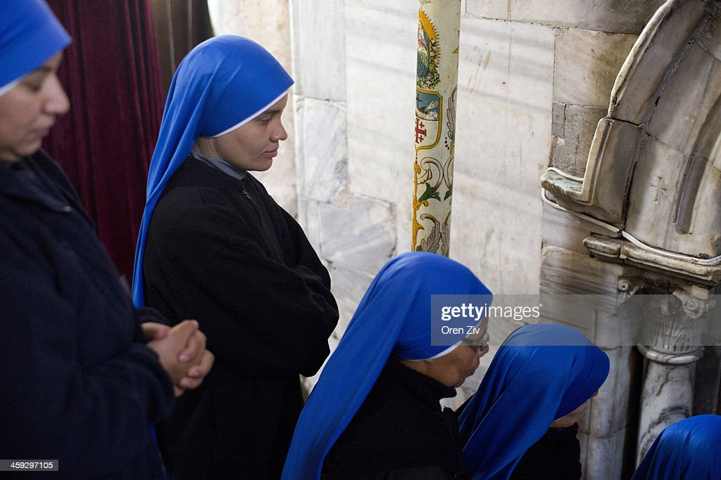 Christian nuns enter the Grotto at the Church of the Nativity on December 25, 2013 in Bethlehem, West Bank. Every Christmas pilgrims travel to the church where a gold star embedded in the floor marks the spot where Jesus was believed to have been born.