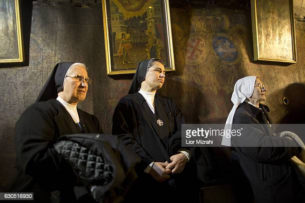 Christian nuns pray at the Grotto in the Church of the Nativity on December 25 2016 in Bethlehem West Bank Every Christmas pilgrims travel to the...