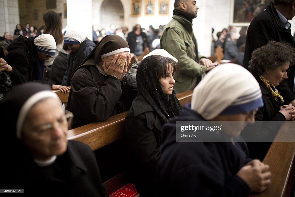 Christian nuns pray during the Christmas mass at the Church of the Nativity on December 25, 2013 in Bethlehem, West Bank. Every Christmas pilgrims travel to the church where a gold star embedded in the floor marks the spot where Jesus was believed to have been born.