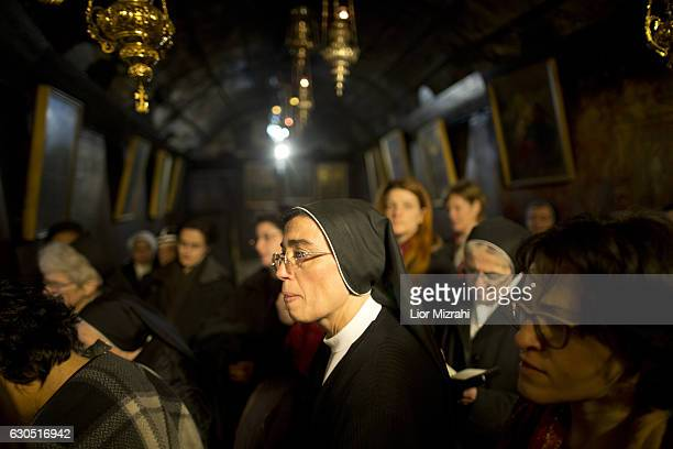 Christian nuns prays at the Grotto in the Church of the Nativity on December 25 2016 in Bethlehem West Bank Every Christmas pilgrims travel to the...