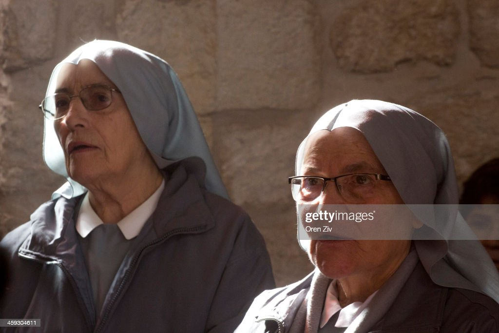 Christian nuns sing during the Christmas mass at the Church of the Nativity on December 25, 2013 in Bethlehem, West Bank. Every Christmas pilgrims travel to the church where a gold star embedded in the floor marks the spot where Jesus was believed to have been born.