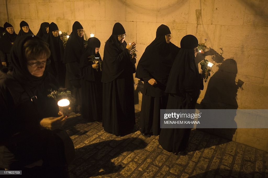 Christian Orthodox nuns holding candles and flowers walk on August 25, 2013 along the narrow streets of Jerusalem's Old City in a religious procession marking the Dormition of the Theotokos (God-bearer) which commemorates the Virgin Mary. Thousands of Christian Orthodox clergy and pilgrims took part in the early morning procession, an annual event during which Orthodox believers carry an icon of the Virgin Mary from the Church of the Holy Sepulchre to Mary's Tomb Church, located on the foothills of the Mount of Olives, near Gethsemane garden, which is regarded as the burial place of Virgin, according to Christian tradition. AFP PHOTO/MENAHEM KAHANA