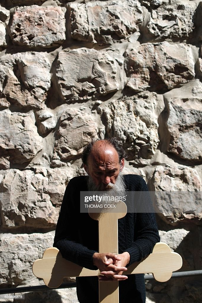A Christian Orthodox pilgrim from Serbia holds a cross as he waits in the Via Dolorosa (Way of Suffering) in Jerusalems Old City during the Good Friday celebrations, on April 29, 2016. Good Friday is a Christian religious holiday commemorating the crucifixion of Jesus Christ and his death at Calvary. / AFP / THOMAS