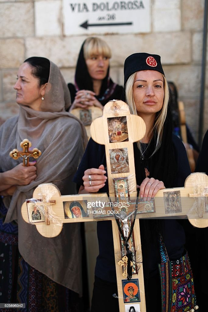 A Christian Orthodox pilgrim from Serbia holds a cross as she waits in the Via Dolorosa (Way of Suffering) in Jerusalems Old City during the Good Friday celebrations, on April 29, 2016. Good Friday is a Christian religious holiday commemorating the crucifixion of Jesus Christ and his death at Calvary. / AFP / THOMAS