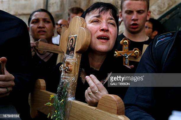 A Christian Orthodox pilgrim holds a wooden cross along the Via Dolorosa during a procession marking the Orthodox Good Friday on May 3 2013 in...