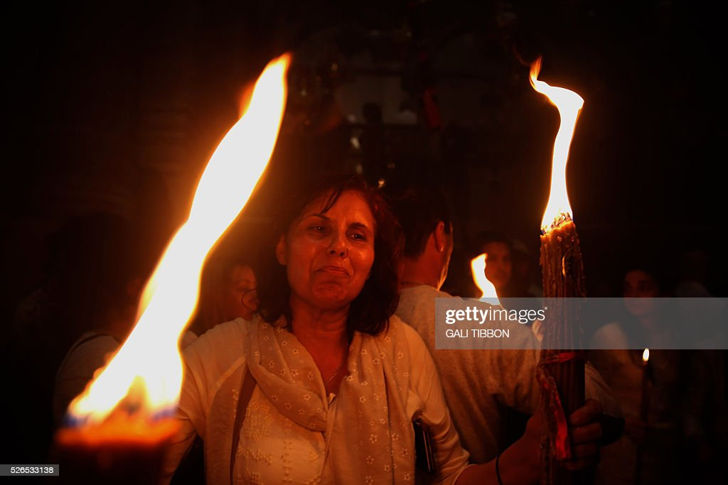 A Christian Orthodox pilgrim holds candles lit from the 'Holy Fire' as thousands gather in the Church of the Holy Sepulchre in Jerusalem's Old City on April 30, 2016 during the Orthodox Easter procession. The ceremony celebrated in the same way for eleven centuries, is marked by the appearance of sacred fire in the two cavities on either side of the Holy Sepulchre. / AFP / GALI