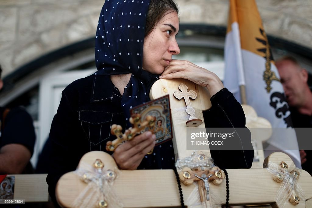 A Christian Orthodox pilgrim holds crosses as she waits in the Via Dolorosa (Way of Suffering) in Jerusalems Old City during the Good Friday celebrations, on April 29, 2016. Good Friday is a Christian religious holiday commemorating the crucifixion of Jesus Christ and his death at Calvary. / AFP / THOMAS