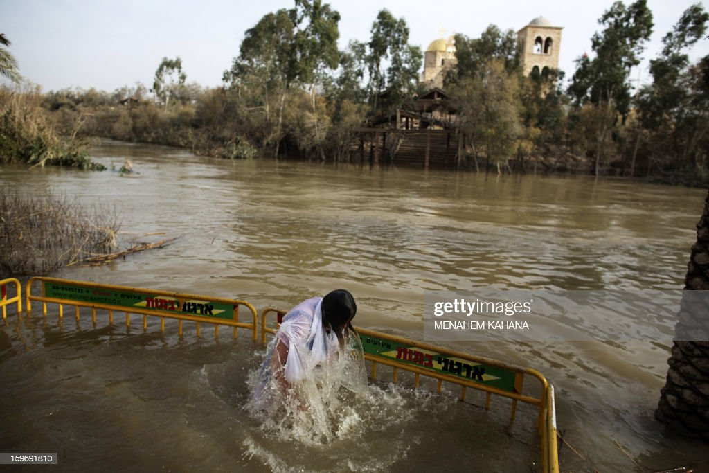Christian Orthodox pilgrim immerses herself into the waters of the Jordan River during a baptism ceremony marking the Orthodox Feast of the Epiphany on January 18, 2013 at the Qasr al-Yahud baptismal site in the West Bank by the Jordan River. Greek Orthodox Patriarch of Jerusalem Theophilos III led the ceremony during which thousands of Orthodox Christians braved rain to plunge into plastic tubs filled with its murky water to celebrate Jesus's baptism. AFP PHOTO/MENAHEM KAHAN