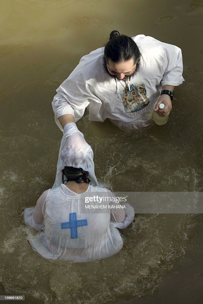 A Christian Orthodox pilgrim is baptized by a priest into the waters of the Jordan River during a baptism ceremony marking the Orthodox Feast of the Epiphany on January 18, 2013 at the Qasr al-Yahud baptismal site in the West Bank by the Jordan River. Greek Orthodox Patriarch of Jerusalem Theophilos III led the ceremony during which thousands of Orthodox Christians braved rain to plunge into plastic tubs filled with its murky water to celebrate Jesus's baptism.