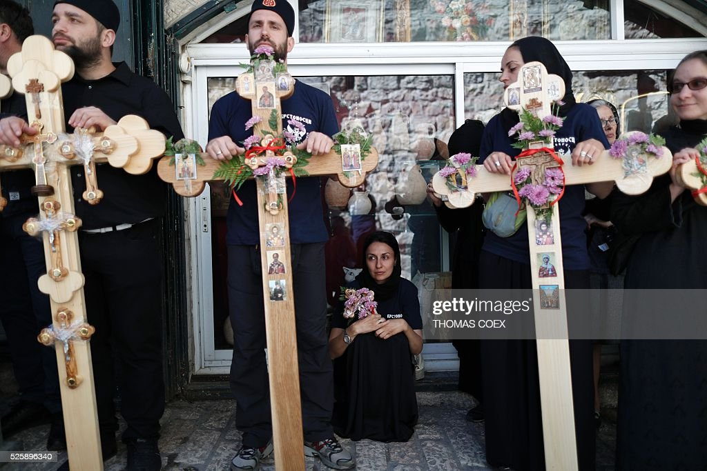 Christian Orthodox pilgrims from Serbia hold crosses as they wait in the Via Dolorosa (Way of Suffering) in Jerusalems Old City during the Good Friday celebrations, on April 29, 2016. Good Friday is a Christian religious holiday commemorating the crucifixion of Jesus Christ and his death at Calvary. / AFP / THOMAS
