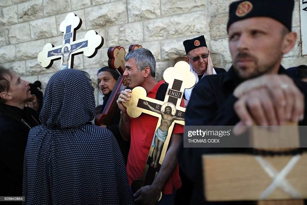 Christian Orthodox pilgrims hold crosses as they wait in the Via Dolorosa (Way of Suffering) in Jerusalems Old City during the Good Friday celebrations, on April 29, 2016. Good Friday is a Christian religious holiday commemorating the crucifixion of Jesus Christ and his death at Calvary. / AFP / THOMAS