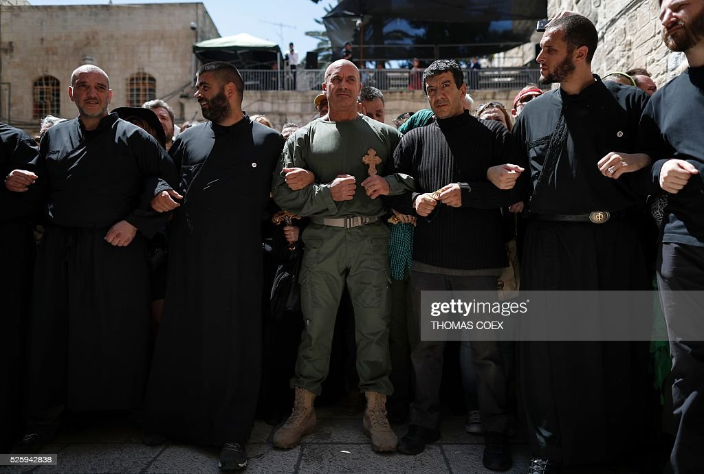 Christian Orthodox pilgrims hold crosses as they wait to enter the Church of the Holy Sepulchre in Jerusalems Old City during the Good Friday celebrations, on April 29, 2016. Good Friday is a Christian religious holiday commemorating the crucifixion of Jesus Christ and his death at Calvary. / AFP / THOMAS