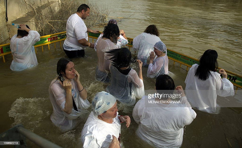 Christian Orthodox pilgrims immerse themselves into the waters of the Jordan River during a baptism ceremony as part of the Orthodox Feast of the Epiphany on January 18, 2013 at the Qasr al-Yahud baptismal site in the West Bank by the Jordan River. Greek Orthodox Patriarch of Jerusalem Theophilos III led the ceremony during which thousands of Orthodox Christians braved rain to plunge into plastic tubs filled with its murky water to celebrate Jesus's baptism. AFP PHOTO/MENAHEM KAHAN
