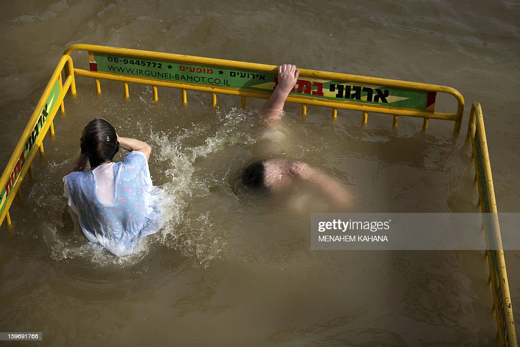 Christian Orthodox pilgrims plunge into the waters of the Jordan River during a ceremony marking the Orthodox Feast of the Epiphany on January 18, 2013 at the Qasr al-Yahud baptismal site in the West Bank by the Jordan River. Greek Orthodox Patriarch of Jerusalem Theophilos III led the ceremony during which thousands of Orthodox Christians braved rain to plunge into plastic tubs filled with its murky water to celebrate Jesus's baptism.