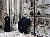 Christian Orthodox priests look through a hole in the main door of the Church of the Holy Sepulchre before the Holy fire ceremony around Jesus' tomb...