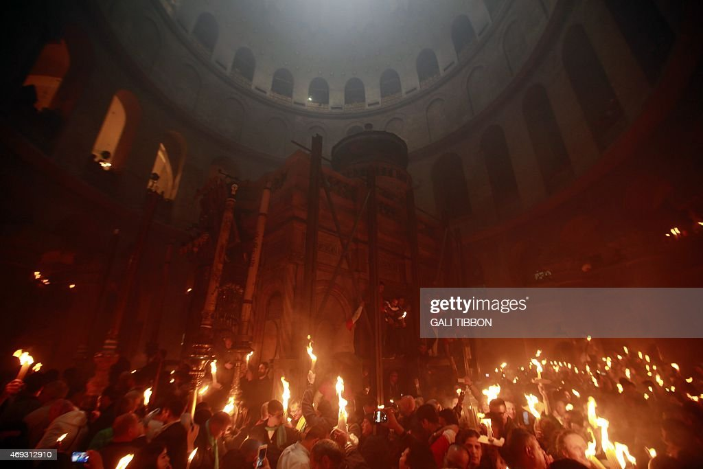 Christian Orthodox worshipers hold up candles lit from the 'Holy Fire' as thousands gather in the Church of the Holy Sepulchre in Jerusalems Old City...