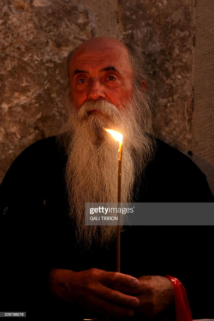 A Christian Orthodox worshipper holds a candle as he prays during the Orthodox Easter Sunday mass at the Church of the Holy Sepulchre in Jerusalem's Old City on May 1, 2016 as Orthodox Christians celebrate the resurrection of Jesus. / AFP / GALI