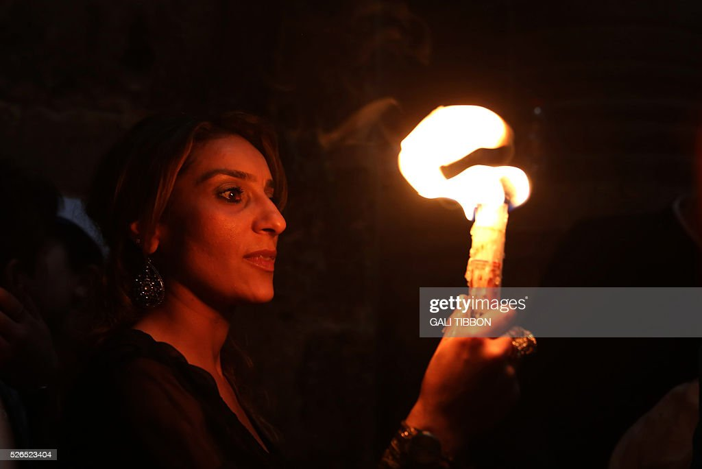 A Christian Orthodox worshipper holds candles lit from the 'Holy Fire' as thousands gather in the Church of the Holy Sepulchre in Jerusalem's Old City on April 30, 2016 during the Orthodox Easter ceremony. The ceremony celebrated in the same way for eleven centuries, is marked by the appearance of sacred fire in the two cavities on either side of the Holy Sepulchre. / AFP / GALI