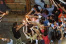 Christian Orthodox worshipper lights the candles of fellow worshippers to help pass the Holy Fire around the tomb of Christ in the Church of the Holy...