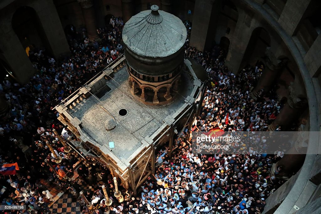Christian Orthodox worshippers dance and pray around the Tomb of Jesus as thousands gather in the Church of the Holy Sepulchre in Jerusalem's Old City, on April 30, 2016, during the Orthodox Easter ceremony of the 'Holy Fire'. The ceremony celebrated in the same way for eleven centuries, is marked by the appearance of 'sacred fire' in the two cavities on either side of the Holy Sepulchre. / AFP / THOMAS