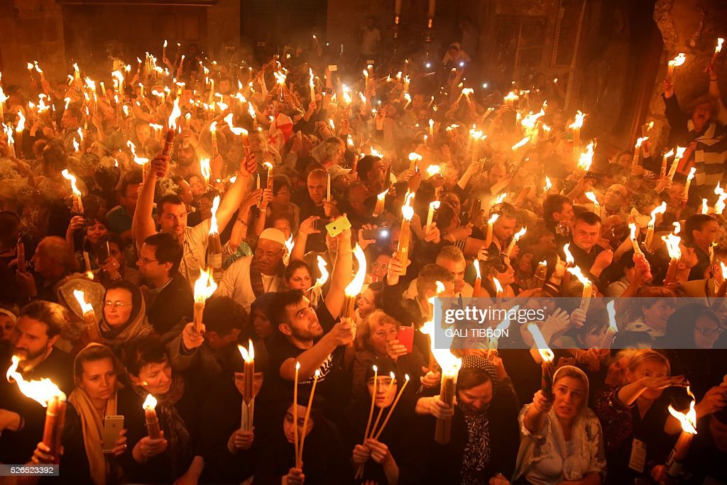 Christian Orthodox worshippers hold candles lit from the 'Holy Fire' as thousands gather in the Church of the Holy Sepulchre in Jerusalem's Old City on April 30, 2016 during the Orthodox Easter ceremony. The ceremony celebrated in the same way for eleven centuries, is marked by the appearance of sacred fire in the two cavities on either side of the Holy Sepulchre. / AFP / GALI