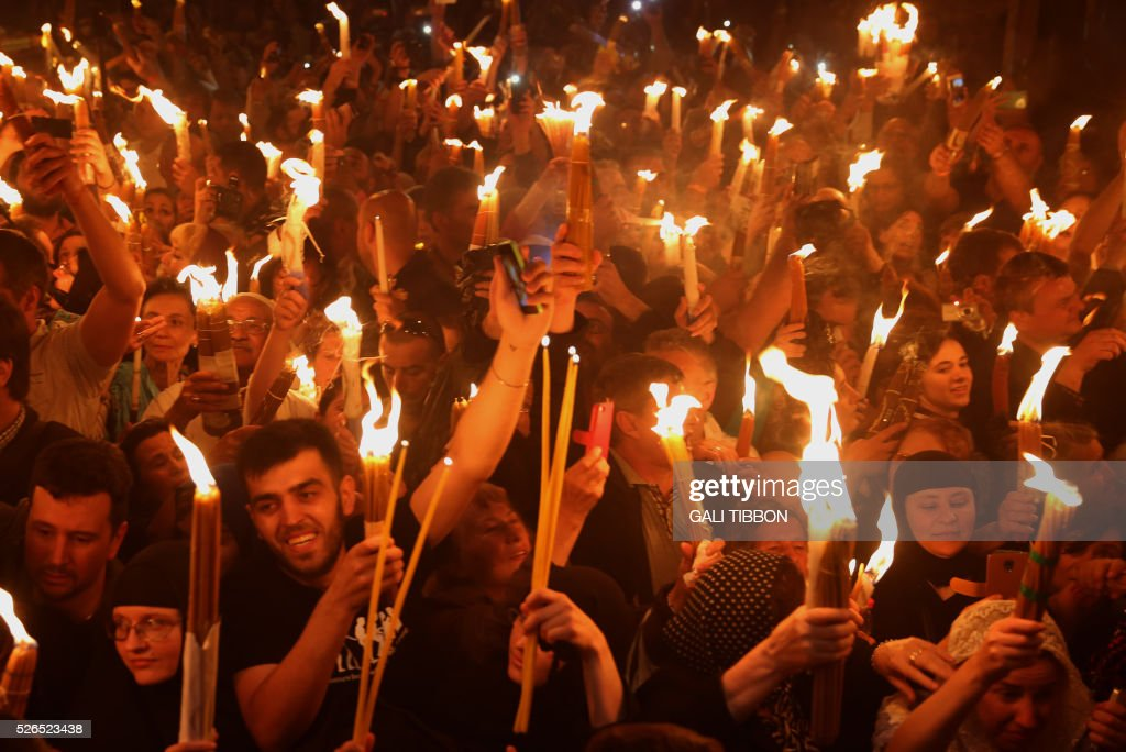 Christian Orthodox worshippers hold up candles lit from the ��Holy Fire�� as thousands gather in the Church of the Holy Sepulchre in Jerusalem��s Old City on April 30 ,2016 during the Orthodox Easter ceremony of the ��Holy Fire��. The ceremony celebrated in the same way for 11 centuries, is marked by the appearance of ��sacred fire�� in the two cavities on either side of the Holy Sepulchre.AFP PHOTO/GALI TIBBON The ceremony celebrated in the same way for eleven centuries, is marked by the appearance of sacred fire in the two cavities on either side of the Holy Sepulchre. / AFP / GALI
