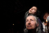 Christian Orthodox worshippers hold their heads up as a ray of light comes through a skylight in the Church of the Holy Sepulchre in Jerusalem's old...