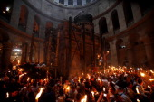 Christian Orthodox worshippers hold up candles lit from the 'Holy Fire' as thousands gather in the Church of the Holy Sepulchre in Jerusalem's old...