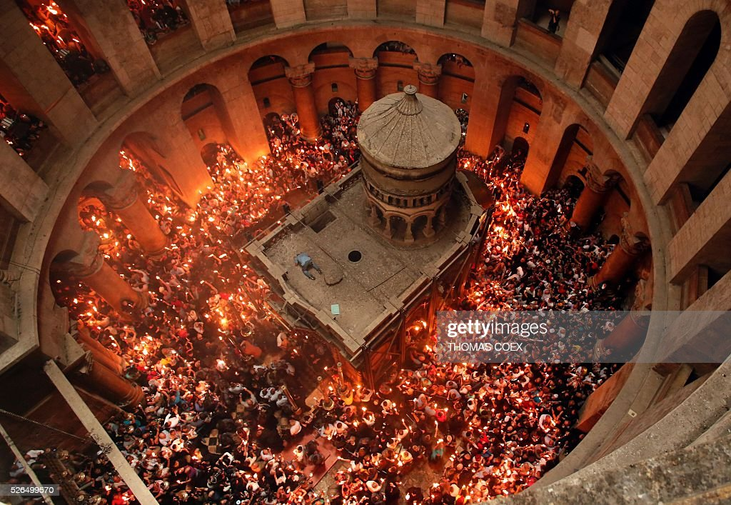 Christian Orthodox worshippers hold up candles lit from the 'Holy Fire' as thousands gather in the Church of the Holy Sepulchre in Jerusalem's Old City, on April 30, 2016, during the Orthodox Easter ceremonies. The ceremony celebrated in the same way for eleven centuries, is marked by the appearance of 'sacred fire' in the two cavities on either side of the Holy Sepulchre. / AFP / THOMAS