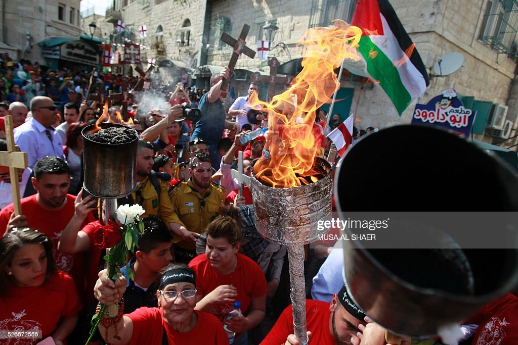 Christian Orthodox worshippers take part in the 'Holy Fire' ceremony outside the Church of the Nativity in the biblical West Bank town of Bethlehem on April 30, 2016. The ceremony is marked by the appearance of 'sacred fire' in the two cavities on either side of the Holy Sepulchre, in the Church of the Sepulchre in Jerusalem, and Christians all over the world light candles representing this 'Holy Fire'. The Holy Sepulchre in Jerusalem is the site of the tomb of Jesus Christ according to Christian tradition. / AFP / MUSA