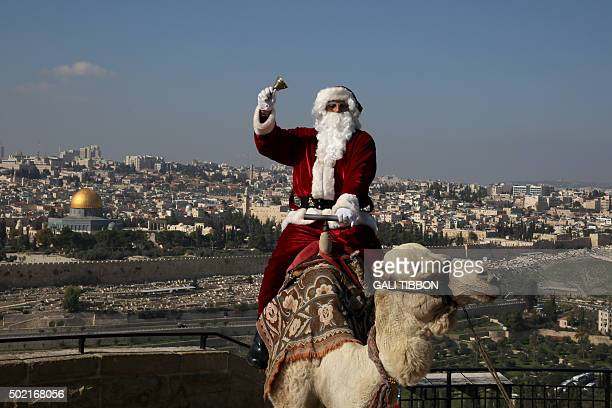 A Christian Palestinian man dressed up as Santa Claus rings a bell as he sits on a camel at Mt Olives backdropped by Jerusalem's Old City skyline on...