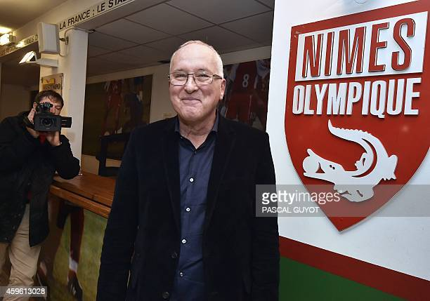 Christian Perdrier newly appointed president of French L2 second division football club Nimes Olympiques poses in front of Nime's logo on November 26...