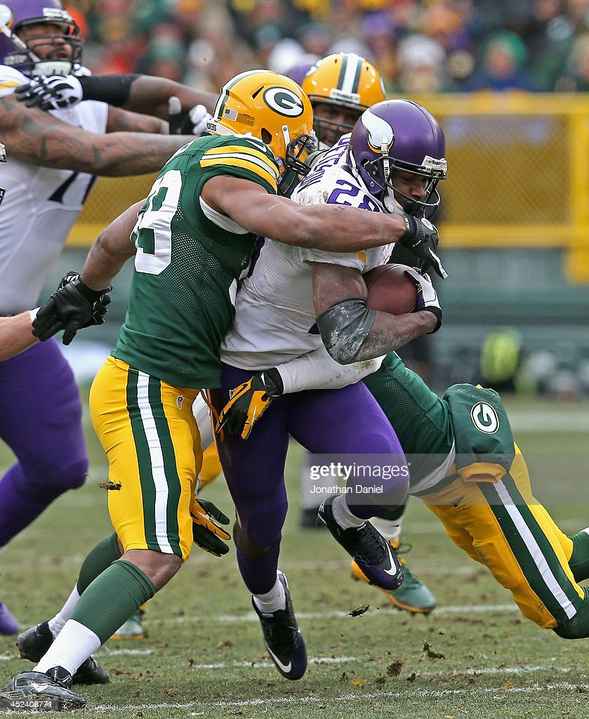 Christian Peterson #28 of the Minnesota Vikings is tackeld by Brad Jones #59 of the Green Bay Packers at Lambeau Field on November 24, 2013 in Green Bay, Wisconsin. The Vikings and the Packers tied 26-26 after overtime.