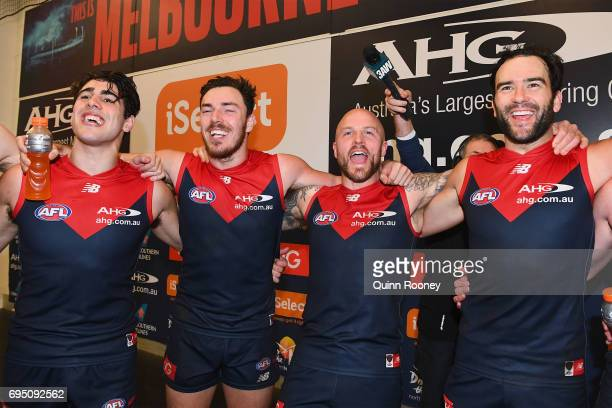 Christian Petracca Michael Hibberd Nathan Jones and Jordan Lewis of the Demons sing the song in the rooms after winning the round 12 AFL match...
