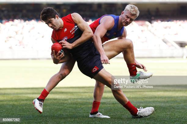 Christian Petracca of the Demons and Nick Robertson of the Lions contest the ball during the round 22 AFL match between the Melbourne Demons and the...