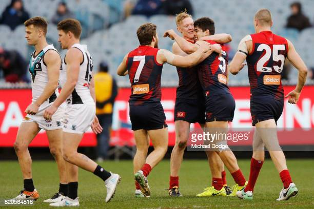 Christian Petracca of the Demons celebrates a goal Jack Viney and Clayton Oliver during the round 18 AFL match between the Melbourne Demons and the...