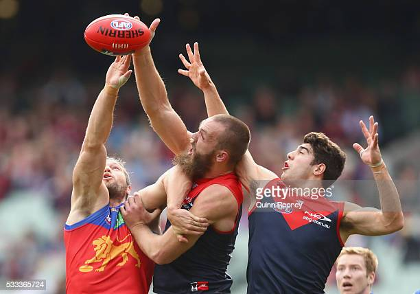 Christian Petracca of the Demons goes third man up as Stefan Martin of the Lions and Max Gawn of the Demons compete in the ruck during the round nine...