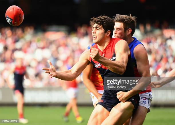 Christian Petracca of the Demons handballs whilst being tackled by Ryan Bastinac of the Lions during the round 22 AFL match between the Melbourne...