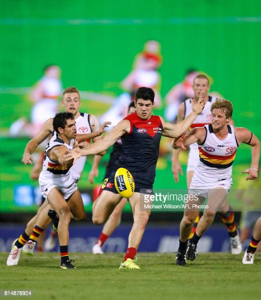 Christian Petracca of the Demons kicks the ball as Charlie Cameron and Rory Sloane of the Crows give chase during the 2017 AFL round 17 match between...