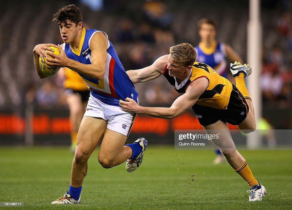 Christian Petracca of the Ranges kicks whilst being tackled by Kyle Gray of the Stingrays during the TAC Cup final match between Eastern Ranges and the Dandenong Southern Stingrays at Etihad Stadium on September 22, 2013 in Melbourne, Australia.