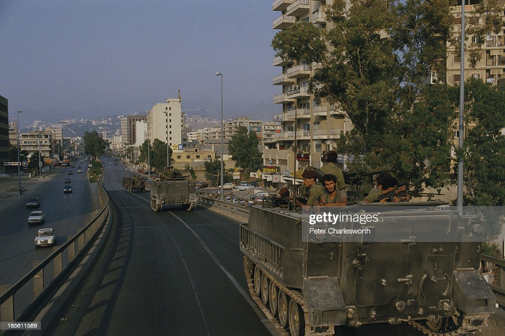 Christian Phalangist militia forces drive armoured personnel carriers through an East Beirut street as they move heavy equipment and artillery into...