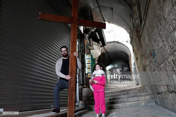 A Christian pilgrim and a child carry a wooden cross along the Via Dolorosa in Jerusalems Old City during the Good Friday procession on April 14 2017...