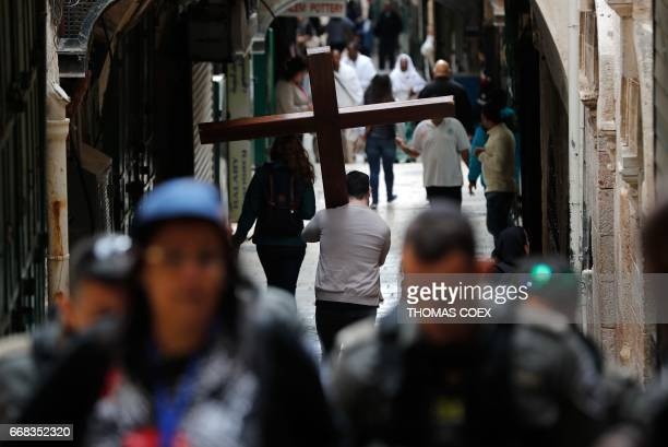 A Christian pilgrim carries a wooden cross along the Via Dolorosa in Jerusalems Old City during the Good Friday procession on April 14 2017...