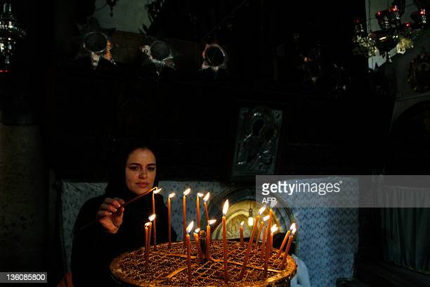 A Christian pilgrim lights a candle at the Church of the Nativity in the biblical West Bank city of Bethlehem on December 19 2011 as pilgrims and...