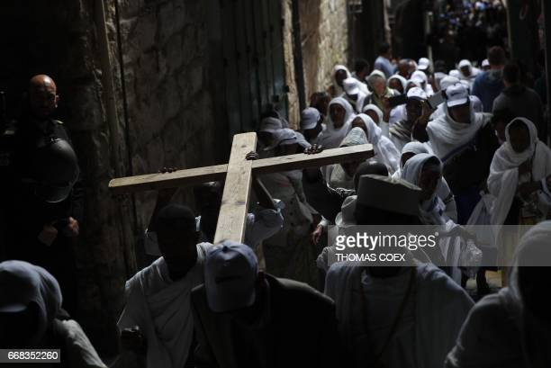 TOPSHOT Christian pilgrims carry a wooden cross along the Via Dolorosa in Jerusalems Old City during the Good Friday procession on April 14 2017...