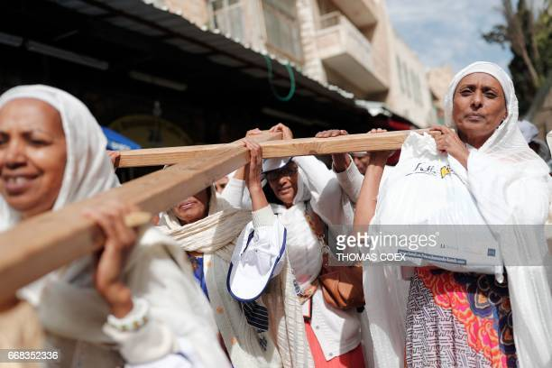 Christian pilgrims carry a wooden cross along the Via Dolorosa in Jerusalems Old City during the Good Friday procession on April 14 2017 Christians...