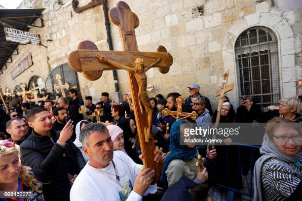 Christian pilgrims carry wooden crosses as they enter the Church of the Holy Sepulchre in the Old City of Jerusalem during the Good Friday procession...