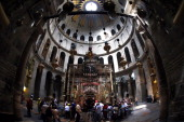 Christian pilgrims gather around the 'Edicule of the Tomb of Jesus Christ' in The Church of the Holy Sepulchre also known as the Basilica of the...