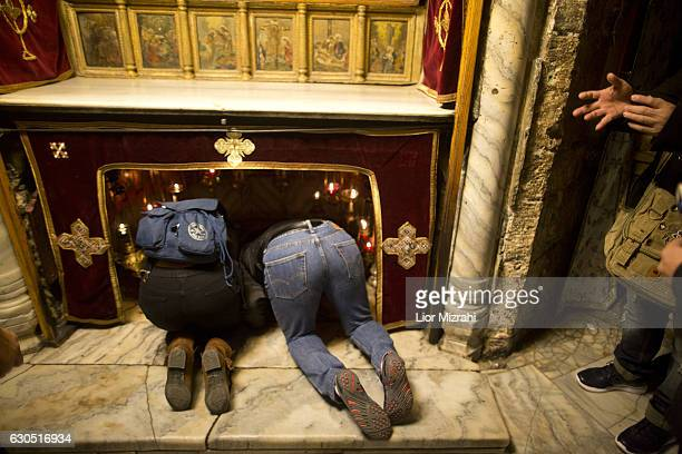 Christian pilgrims pray inside the Grotto in the Church of the Nativity on December 25 2016 in Bethlehem West Bank Every Christmas pilgrims travel to...