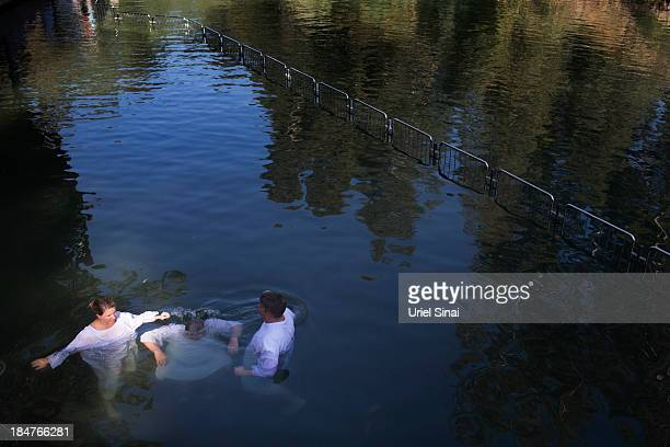 Christian pilgrims take part in a group baptism in the waters of the Jordan Riveron October 16 2013 at the Yardenit Baptismal Site near Tiberias in...